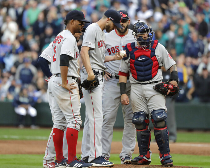 Boston Red Sox starting pitcher Chris Sale holds the ball during a mound conference in the third inning of the team's baseball game against the Seattle Mariners, Thursday, March 28, 2019, in Seattle. Sale was pulled from the game after the inning. (AP Photo/Ted S. Warren)