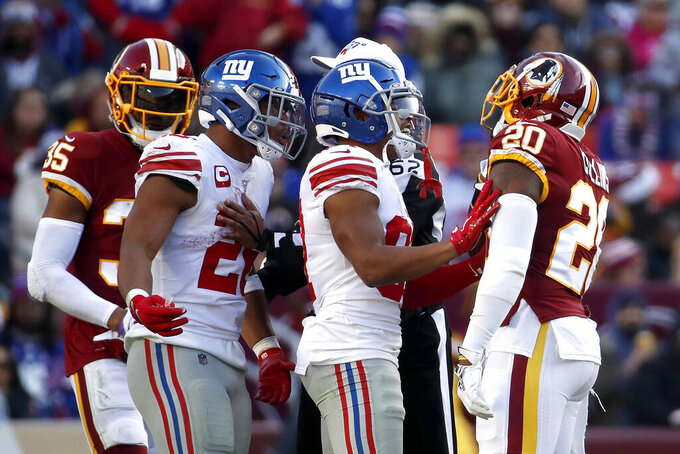 New York Giants wide receiver Sterling Shepard, center right, gets between Washington Redskins strong safety Landon Collins (20) and running back Saquon Barkley, second from left, during an argument in the first half of an NFL football game, Sunday, Dec. 22, 2019, in Landover, Md. Redskins' Montae Nicholson (35) looks on. (AP Photo/Alex Brandon)