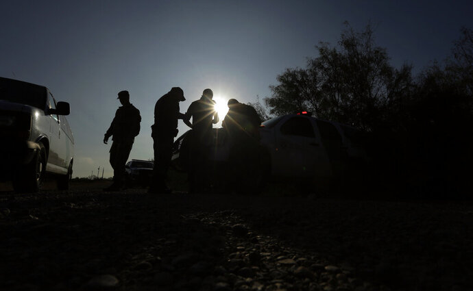 FILE - In this Nov. 6, 2019 file photo, Border Patrol agents apprehend a man thought to have entered the country illegally, near McAllen, Texas, along the U.S.-Mexico border. Immigration authorities are starting to ship asylum seekers who cross the border through Arizona to Texas, where they can be sent to Mexico to await their court hearings in the U.S. The government said its highly criticized program known colloquially as Remain in Mexico is now in effect all across the southwestern border. (AP Photo/Eric Gay, File)