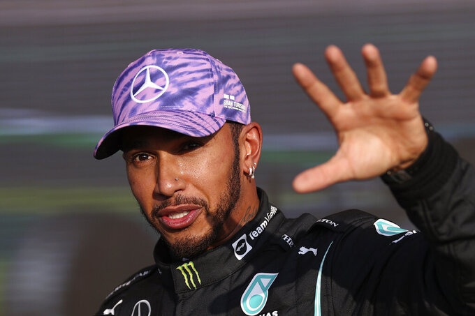 Mercedes driver Lewis Hamilton of Britain gives an interview after clocking the fastest time in the qualifying session ahead of Sunday's British Formula One Grand Prix, at the Silverstone circuit, in Silverstone, England, Friday, July 16, 2021. (Lars Baron/Pool photo via AP)