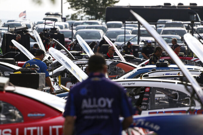 Pit crews work in the garage area before a NASCAR Xfinity Series auto race at Watkins Glen International in Watkins Glen, N.Y., on Saturday, Aug. 7, 2021. (AP Photo/Joshua Bessex)