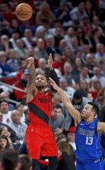Portland Trail Blazers guard Damian Lillard, left, shoots next to Dallas Mavericks guard Jalen Brunson during the second half of an NBA basketball game in Portland, Ore., Wednesday, March 20, 2019. (AP Photo/Craig Mitchelldyer)
