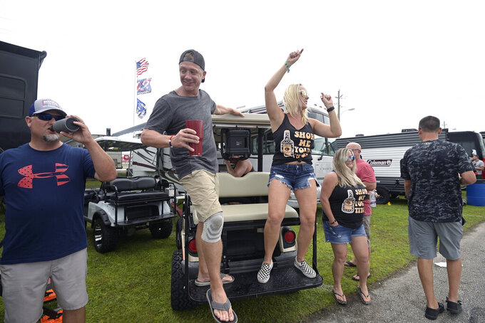 Tim Dejoris, center left, and Marie Waters, center right, dance on the back of a golf cart as fans wait in the infield before the evening start of a NASCAR Xfinity Series auto race at Daytona International Speedway, Friday, Aug. 27, 2021, in Daytona Beach, Fla. (AP Photo/Phelan M. Ebenhack)
