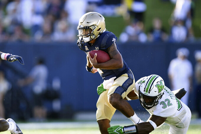 Navy quarterback Xavier Arline (7) runs the ball against Marshall defensive lineman Koby Cumberlander (32) during the second half of an NCAA college football game, Saturday, Sept. 4, 2021, in Annapolis, Md. (AP Photo/Terrance Williams)