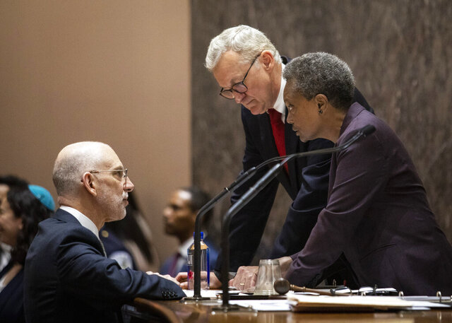 File-This May 29, 2019, file photo shows Chicago Mayor Lori Lightfoot, right, chatting with Corporation Counsel Mark Flessner, center, and Deputy Corporation Counsel Jeff Levine during her first city council meeting at City Hall in Chicago.  Flessner, Chicago's top attorney resigned Sunday, Dec. 20, 2020, in the fallout of a botched police raid on the home of a Black woman who was not allowed to put on clothes before being handcuffed. Flessner announced the move in an email to employees, saying he was only recently involved with the legal case connected to a police video of the February 2019 wrongful raid on the home of social worker Anjanette Young. Flessner did not say if he was asked to resign.  (Ashlee Rezin/Chicago Sun-Times via AP, File)