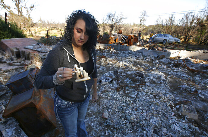 In this Friday, Oct. 18, 2019, photo, Amber Blood looks at a figurine she found in the ashes of her home lost in last year's Camp Fire in Paradise, Calif. Blood is one of the estimated 20,000 former Paradise residents now living in Chico after the fire. A real estate agent, Blood said she even had trouble finding a home after the fire because there was not much available. (AP Photo/Rich Pedroncelli)