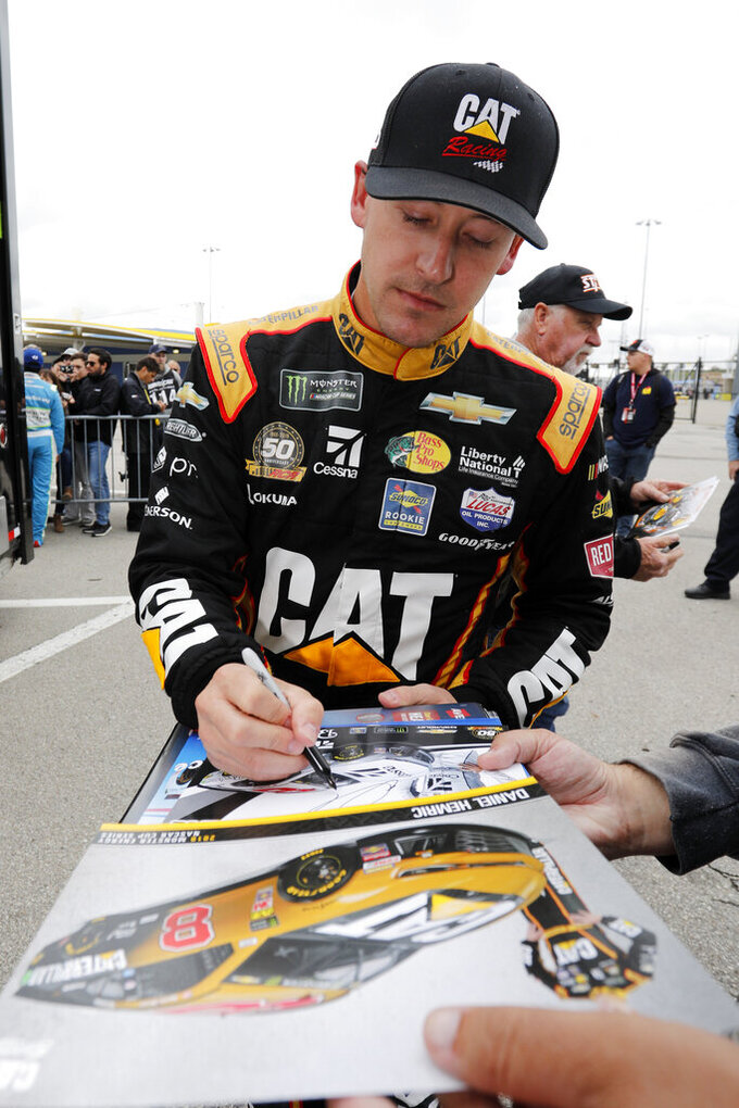 Daniel Hemric signs autographs after qualifying for a NASCAR Cup Series auto race at Kansas Speedway in Kansas City, Kan., Saturday, Oct. 19, 2019. (AP Photo/Colin E. Braley)
