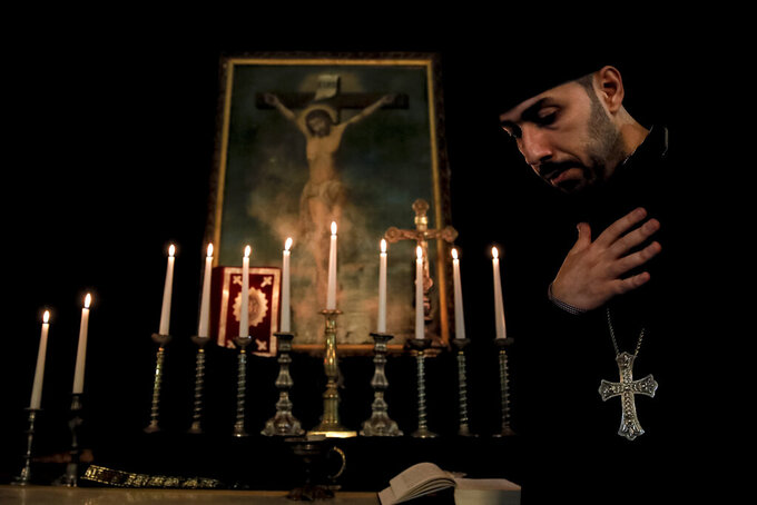 An Armenian clergyman walks by an icon depicting the crucifixion of Jesus Christ during a Maundy Thursday religious service, at the Armenian Church in Bucharest, Romania, Thursday, April 29, 2021. Although Armenians celebrate Christmas on January 6, according to the Julian calendar, Armenian Apostolic Church leaders decided after the mass killings, in 1925, to observe Easter at the same time as the Orthodox Christian majorities in Romania and Greece, believing the change would promote the integration of Armenians in the countries that accepted refugees and to eliminate possible doubts about their Christianity. (AP Photo/Vadim Ghirda)