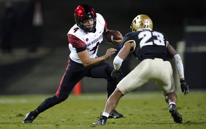 San Diego State quarterback Jordon Brookshire, left, tries to avoid a tackle by Colorado safety Isaiah Lewis during the second half of an NCAA college football game Saturday, Nov. 28, 2020, in Boulder, Colo. (AP Photo/David Zalubowski)