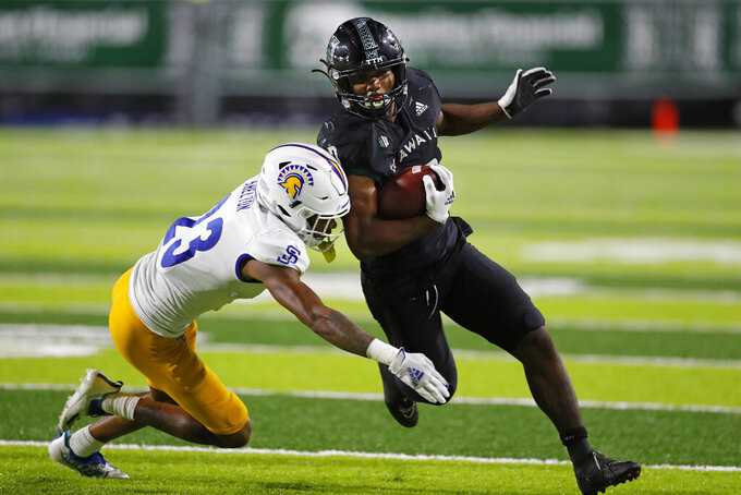 Hawaii running back Dae Dae Hunter (0) tries to get past San Jose State corner back Nehemiah Shelton (23) during the second half of an NCAA college football game, Saturday, Sept. 18, 2021, in Honolulu. (AP Photo/Marco Garcia)