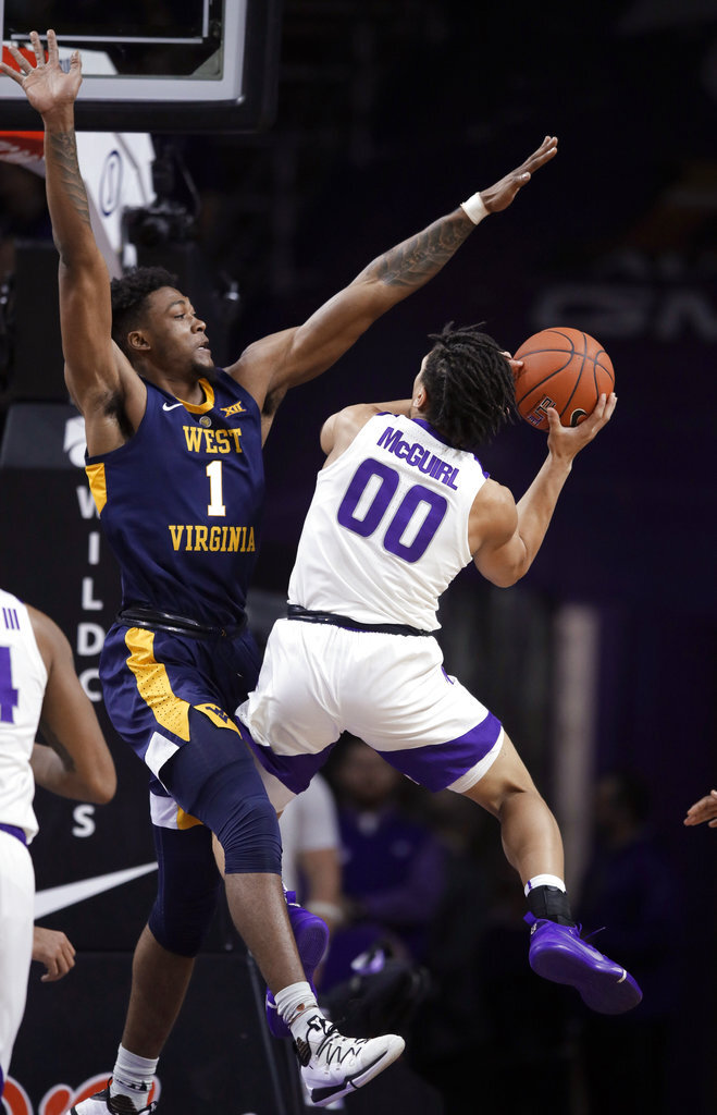 Kansas State guard Mike McGuirl (00) is defended by West Virginia forward Derek Culver (1) during the first half of an NCAA college basketball game in Manhattan, Kan., Wednesday, Jan. 9, 2019. (AP Photo/Orlin Wagner)
