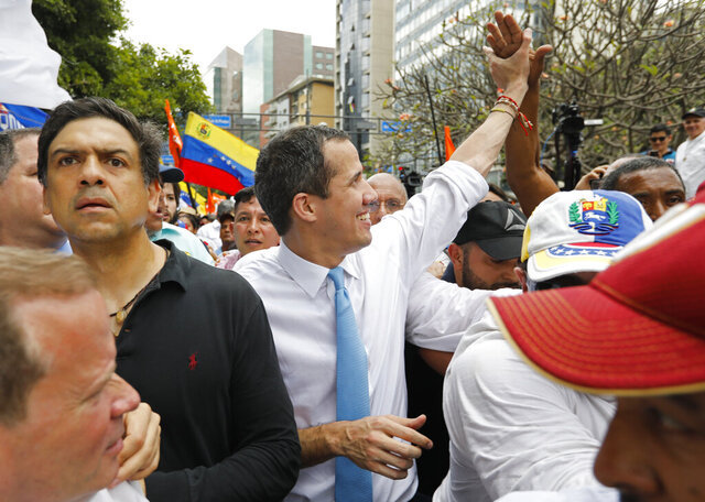 Opposition political leader Juan Guaido greets supporters during a march before it was blocked by police in Caracas, Venezuela, Tuesday, March 10, 2020. Guaido called for the march aimed at retaking the National Assembly legislative building, which opposition lawmakers have been blocked from entering. (AP Photo/Ariana Cubillos)