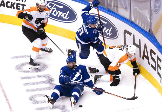 Tampa Bay Lightning left wing Alex Killorn, bottom, and center Tyler Johnson (9) work for the puck against Philadelphia Flyers center Sean Couturier (14) and defenseman Philippe Myers (5) during the second period of an NHL hockey playoff game Saturday, Aug. 8, 2020, in Toronto. (Frank Gunn/The Canadian Press via AP)