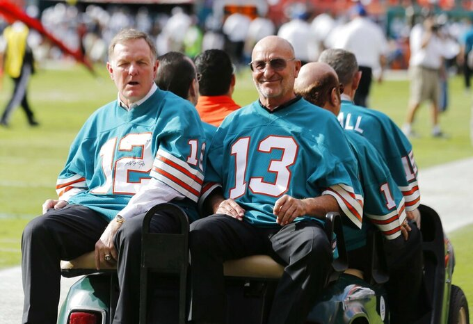 FILE - In this Dec. 16, 2012, file photo, Bob Griese (12) and Jake Scott (13), of the 1972 Miami Dolphins, are driven onto the field for a halftime celebration during the Dolphins' NFL football game against the Jacksonville Jaguars in Miami. Scott, the star safety who was the most valuable player in the Super Bowl that completed the Dolphins' 1972 perfect season, died Thursday, Nov. 19, 2020, in Atlanta. He was 75. Scott died after a fall down a stairway that left him in a coma, former teammate Dick Anderson said. (AP Photo/John Bazemore, File)