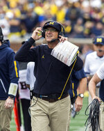 Michigan head coach Jim Harbaugh adjusts his headset as he looks up at the scoreboard in the first quarter of an NCAA college football game against Western Michigan in Ann Arbor, Mich., Saturday, Sept. 8, 2018. (AP Photo/Tony Ding)