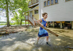 Tallulah Campbell, 8, clears out driftwood and other debris in preparation of Tropical Storm Barry near New Orleans, La., Thursday, July 11, 2019. The area is normally a driveway at her family's home that is one of the few on land called batture on the outside of the Mississippi River levee at the border of Orleans and Jefferson Parishes. (AP Photo/Matthew Hinton)