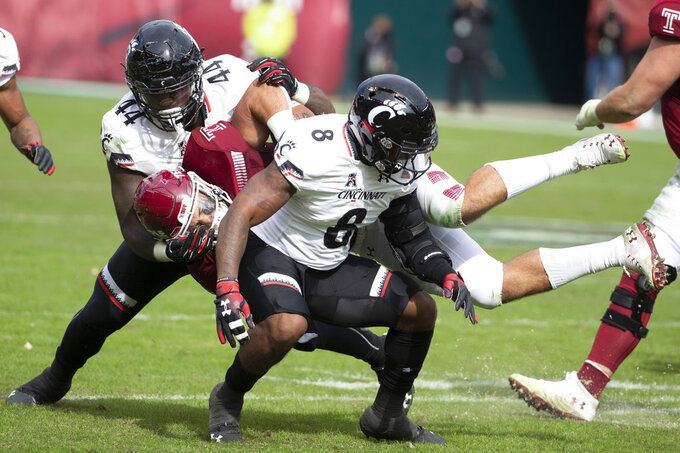 Cincinnati's linebacker Jarell White (8) and defensive tackle Marquise Copeland (44) bring down Temple's fullback Rob Ritrovato (4) during the first half of an NCAA college football, Saturday, Oct. 20, 2018, in Philadelphia. (AP Photo/Chris Szagola)