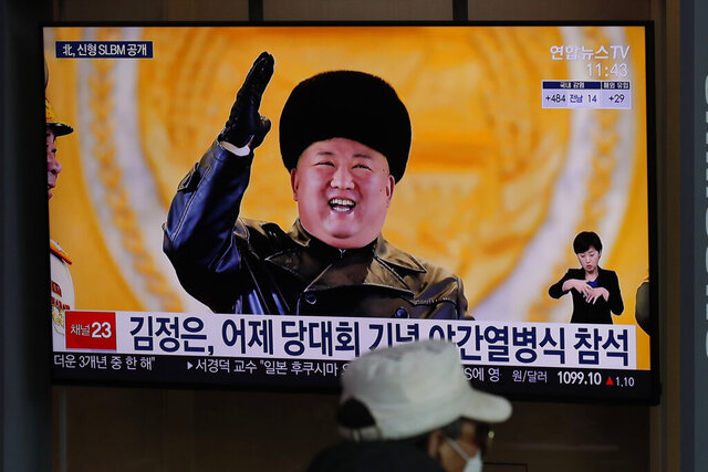 A man wearing a face mask sits in front of a TV screen showing North Korean leader Kim Jong Un, at the Seoul Railway Station in Seoul, South Korea, Friday, Jan. 15, 2021. The letters read