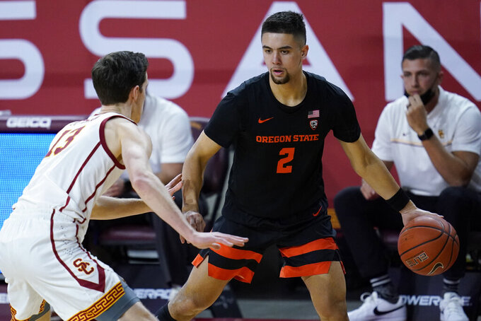 Oregon State guard Jarod Lucas (2) controls the ball next to Southern California guard Drew Peterson (13) during the first half of an NCAA college basketball game Thursday, Jan. 28, 2021, in Los Angeles. (AP Photo/Ashley Landis)