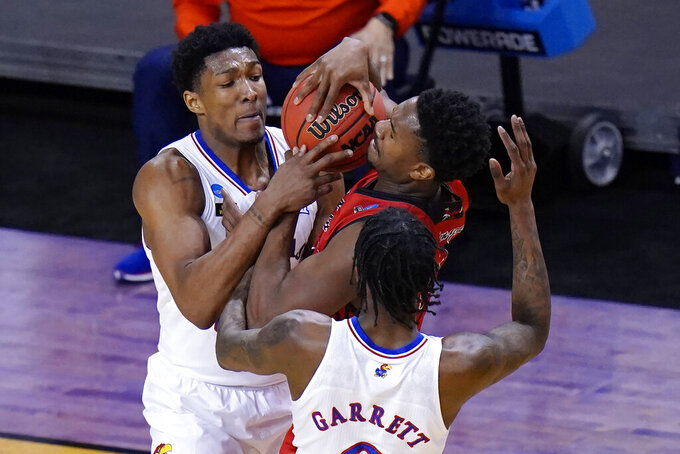 Eastern Washington guard Kim Aiken Jr., center, struggles to keep the ball as Kansas forward David McCormack, left, and Kansas guard Marcus Garrett (0) pressure during the first half of a first-round game in the NCAA college basketball tournament at Farmers Coliseum in Indianapolis, Ind., Saturday, March 20, 2021. (AP Photo/AJ Mast)