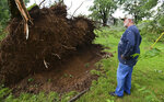 Tim Hinkle stands near the root ball of a downed tree on his property on King Road near Riegle Road on Wednesday, June 10, 2020. Strong storms with heavy winds swept across Jackson County, Mich., causing power outages, downing trees and damaging property. Hinkle had about a dozen trees either completely toppled or with limbs sent flying. His home also sustained damage.  (J. Scott Park/Jackson Citizen Patriot via AP)