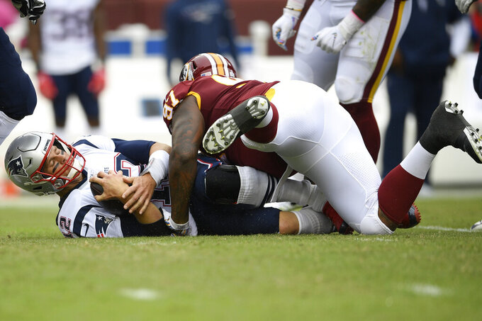 Washington Redskins outside linebacker Ryan Kerrigan (91) sacks New England Patriots quarterback Tom Brady (12) during the first half of an NFL football game, Sunday, Oct. 6, 2019, in Washington. (AP Photo/Nick Wass)