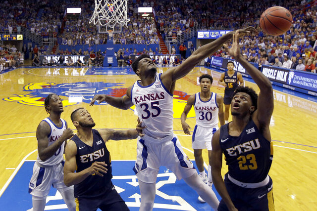 FILE - In this Nov. 19, 2019, file photo, Kansas center Udoka Azubuike (35) blocks a shot by East Tennessee State forward Vonnie Patterson (23) during the second half of an NCAA college basketball game in Lawrence, Kan. Azubuike was selected to the Associated Press All-Big 12 first team announced Tuesday, March 10, 2020. Azubuike was also named the AP Big 12 Player of the Year. (AP Photo/Charlie Riedel, File)