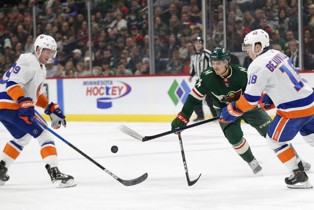 Minnesota Wild center Joel Eriksson Ek (14), New York Islanders center Brock Nelson (29) and Islanders left wing Anthony Beauvillier vie for the puck in the first period of an NHL hockey game Sunday, Dec. 29, 2019, in St. Paul, Minn. (AP Photo/Andy Clayton-King)