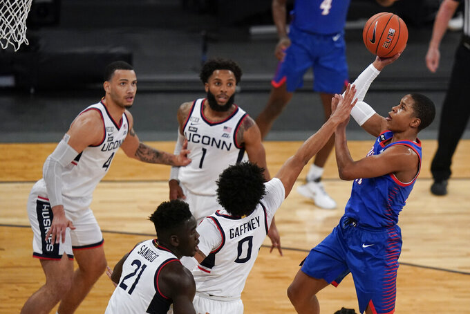 DePaul's Charlie Moore, right, shoots over Connecticut's Jalen Gaffney (0) during the first half of an NCAA college basketball game in the Big East men's tournament Thursday, March 11, 2021, in New York. (AP Photo/Frank Franklin II)