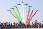 The pack of cyclists is backdropped by the Frecce Tricolori Italian Air Force aerobatic squad flying past, prior to the 15th stage of the Giro d'Italia cycling race, Italy, at the Rivolto air base, Sunday, Oct. 18, 2020. (Gian Mattia D'Alberto/LaPresse via AP)
