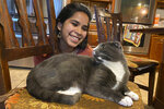"""In this photo provided by Raghav Ranjan, Devika Ranjan smiles at her cat, Aloo, on Dec. 13, 2020, in Andover, Mass. Ranjan, a theater director in  Chicago, wanted pandemic company and got a rescue cat she named Aloo during the summer. The formerly feral cat is believed to be around 3, and seems to be very comfortable with a slow-paced, high-attention pandemic life. """"My working from home, I think he loves it,"""" she says. """"I think he is just ready to settle down in life. If he were human, he'd probably sit on the couch with a PBR (beer) and watch TV all day."""