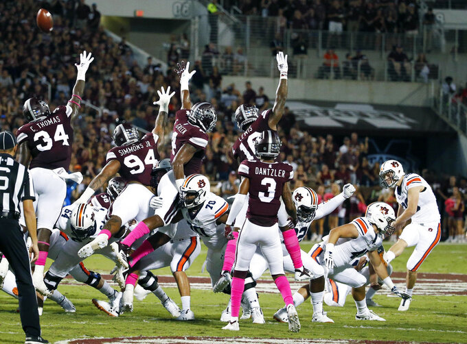 Auburn place kicker Anders Carlson, right, kicks a 47-yard field goal against Mississippi State defenders during the first half of their NCAA college football game in Starkville, Miss., Saturday, Oct. 6 2018. (AP Photo/Rogelio V. Solis)