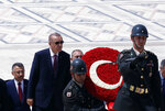 FILE - In this file photo dated Thursday, Aug. 1, 2019, Turkey's President Recep Tayyip Erdogan, center left, with ministers and army commanders as they follow a guard of honor at the mausoleum of Turkey's founder Mustafa Kemal Ataturk, in Ankara, Turkey. Turkey's combative president is threatening to launch a military operation in northeastern Syria that would be designed to push back U.S.-allied Syrian Kurdish forces. (AP Photo/Burhan Ozbilici, FILE)