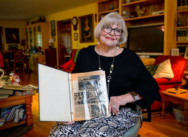 In this Jan. 14, 2020 photo, Barbara Thompson holds a Forsyth County News article from the 1970s about the opening of her beauty salon, The Barbara Shoppe, inside the small four-unit shopping center she had built on Dahlonega Highway in downtown Cumming, Ga. The building was destroyed by a fire on Friday, Jan. 3, 2020. (Ben Hendren/Forsyth County News via AP)