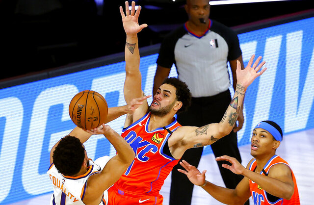 Phoenix Suns' Devin Booker, left, tries to shoot past Oklahoma City Thunder's Abdel Nader, center, during the first half of an NBA basketball game Monday, Aug. 10, 2020, in Lake Buena Vista, Fla. (Mike Ehrmann/Pool Photo via AP)