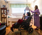 Lisa Haynes, a direct support worker, helps get Lauren, who has cerebral palsy and is non-verbal, into her bed at the home of Sue Roesky in Metairie, La., Friday, Sept. 17, 2021. Haynes is one of four people to help Roesky care for Lauren. (Sophia Germer/The Times-Picayune/The New Orleans Advocate via AP)