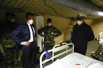 French President Emmanuel Macron, second left, wears a face mask as he visits the military field hospital in Mulhouse, eastern France, Wednesday, March 25, 2020. French President Emmanuel Macron launched a special military operation Wednesday to help fight the new virus in one of the world's hardest-hit countries. The new coronavirus causes mild or moderate symptoms for most people, but for some, especially older adults and people with existing health problems, it can cause more severe illness or death. (Mathieu Cugnot/Pool via AP)