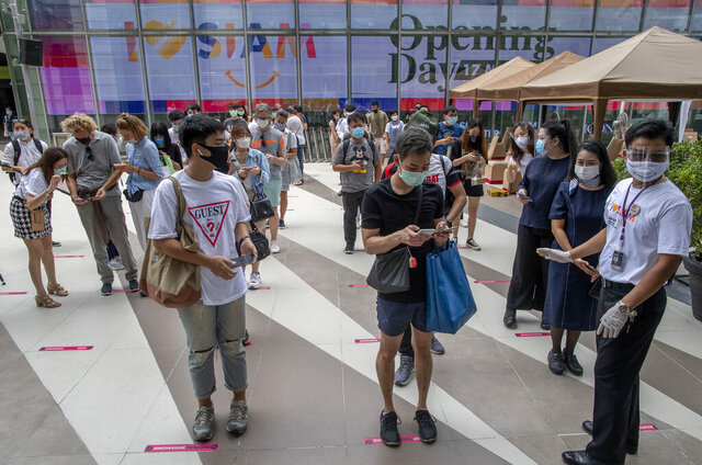 Patrons stand maintaining a physical distance at the entrance of the upmarket shopping mall Siam Paragon in Bangkok, Thailand, Sunday, May 17, 2020. Thai authorities allowed department stores, shopping malls and other businesses to reopen from Sunday, selectively easing restrictions meant to combat the coronavirus. (AP Photo/ Gemunu Amarasinghe)