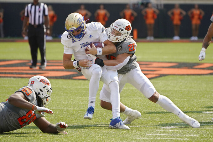 Tulsa quarterback Davis Brin (7) is tackled by Oklahoma State linebacker Malcolm Rodriguez (20) in the first half of an NCAA college football game, Saturday, Sept. 11, 2021, in Stillwater, Okla. (AP Photo/Sue Ogrocki)