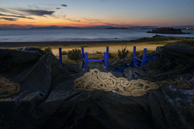 A rope used for decoration is placed on a canvas that covers tables and chairs of a shuttered fish restaurant at the seaside suburb of Kavouri, district of Athens, on Thursday, March 25, 2021. Restaurants, bars and cafes, whose nature it is to gather groups of people closely together, have remained shut since November when the Greek government imposed a second lockdown to curb the spread of COVID-19 infections. (AP Photo/Petros Giannakouris)