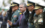 Colombia's President Ivan Duque waves to police cadets, accompanied by his interim Defense Minister and Armed Forces Commander Gen. Luis Fernando Navarro, left, during a graduation ceremony for the cadets in Bogota, Colombia, Thursday, Nov. 7, 2019. Colombia's Defense Minister Guillermo Botero resigned Wednesday after a lawmaker accused him of failing to disclose that eight minors had been killed in a military operation against dissident rebels. (AP Photo/Fernando Vergara)