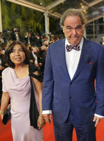 Sun-jung Jung, left, and Oliver Stone poses for photographers upon arrival at the premiere of the film 'Flag Day' at the 74th international film festival, Cannes, southern France, Saturday, July 10, 2021. (AP Photo/Vadim Ghirda)