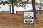 A sign outside a North Little Rock, Ark., cosmetics factory Wednesday, Feb. 14, 2018, notes that weapons are prohibited from the plant that makes Maybelline and L'Oreal cosmetics. Police said two people died in a suspected murder-suicide outside the factory early Wednesday. (AP Photo/Kelly P. Kissel)