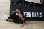 Boston Celtics' Jayson Tatum (0) sits on the floor after his shot attempt was blocked by Miami Heat's Bam Adebayo, not pictured, in the closing seconds of overtime of an NBA conference final playoff basketball game, Tuesday, Sept. 15, 2020, in Lake Buena Vista, Fla. (AP Photo/Mark J. Terrill)