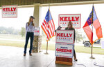 Marjorie Taylor Greene, right, during a news conference with Sen. Kelly Loeffler, R-Ga., left, on Thursday, Oct. 15, 2020, in Dallas, Ga. (AP Photo/Brynn Anderson)