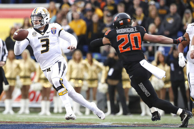 File- This Dec. 31, 2018, file photo shows Missouri quarterback Drew Lock trying to escape the pocket as Oklahoma State safety Malcolm Rodriguez pursues during the first half of the Liberty Bowl NCAA college football game in Memphis, Tenn.  NFL scouts, coaches and prospects have gathered in Mobile, Alabama, for the Senior Bowl. The game for top senior NFL prospects and junior graduates will feature quarterbacks like Missouri's  Lock, West Virginia's Will Grier and Duke's Daniel Jones. (Joe Rondone/The Commercial Appeal via AP, File)