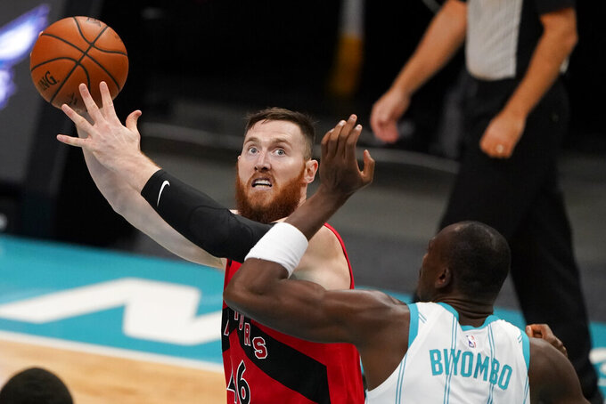 Toronto Raptors' Aron Baynes shoots over Charlotte Hornets center Bismack Biyombo during the first half of an NBA preseason basketball game in Charlotte, Monday, Dec. 14, 2020. (AP Photo/Chris Carlson)