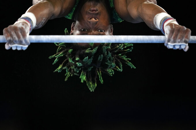 Uche Eke, of Nigeria, competes on the horizontal bar during the men's artistic gymnastic qualifications at the 2020 Summer Olympics, Saturday, July 24, 2021, in Tokyo, Japan. (AP Photo/Gregory Bull)