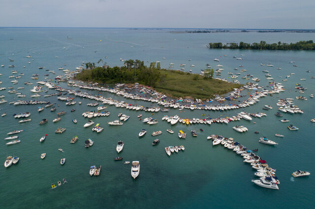 Hundreds of boats congregate around Gull Island, Mich., during the annual Jobbie Nooner in Lake St. Clair, Friday, June 26, 2020. The gathering, an annual celebration of water and sun, is at odds with Michigan's rules intended to curb the spread of the coronavirus. (Andy Morrison/Detroit News via AP)
