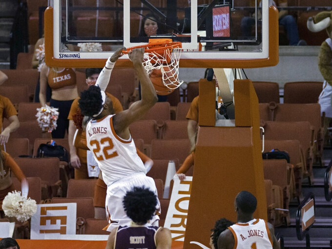 Texas forward Kai Jones (22) dunks during the first half of the team's NCAA college basketball game against Texas State, Wednesday, Dec. 9, 2020, in Austin, Texas. (AP Photo/Michael Thomas)
